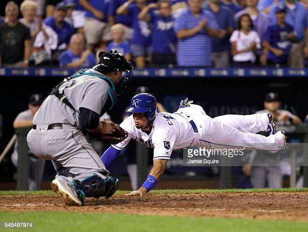 Cheslor Cuthbert of the Kansas City Royals slides safely into home plate to score as catcher Chris Iannetta of the Seattle Mariners misses the tag...