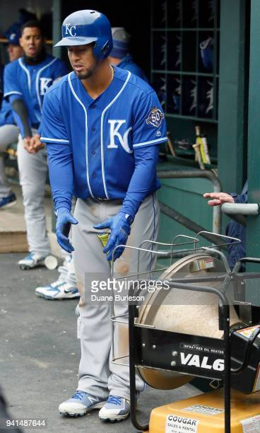 Cheslor Cuthbert of the Kansas City Royals warms his hands in front of a heater in the dugout at Comerica Park during the third inning of a game...