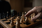 Chess board and human hand close up