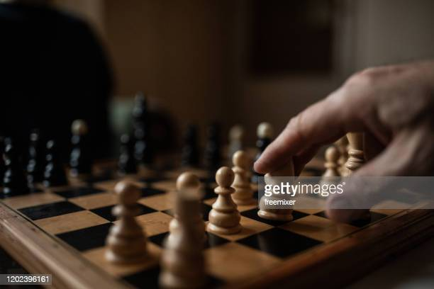 chess board and human hand close up - chess stock pictures, royalty-free photos & images