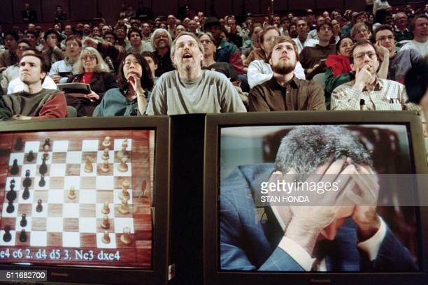 Chess enthusiasts watch World Chess champion Garry Kasparov on a television monitor as he holds his head in his hands at the start of the sixth and...