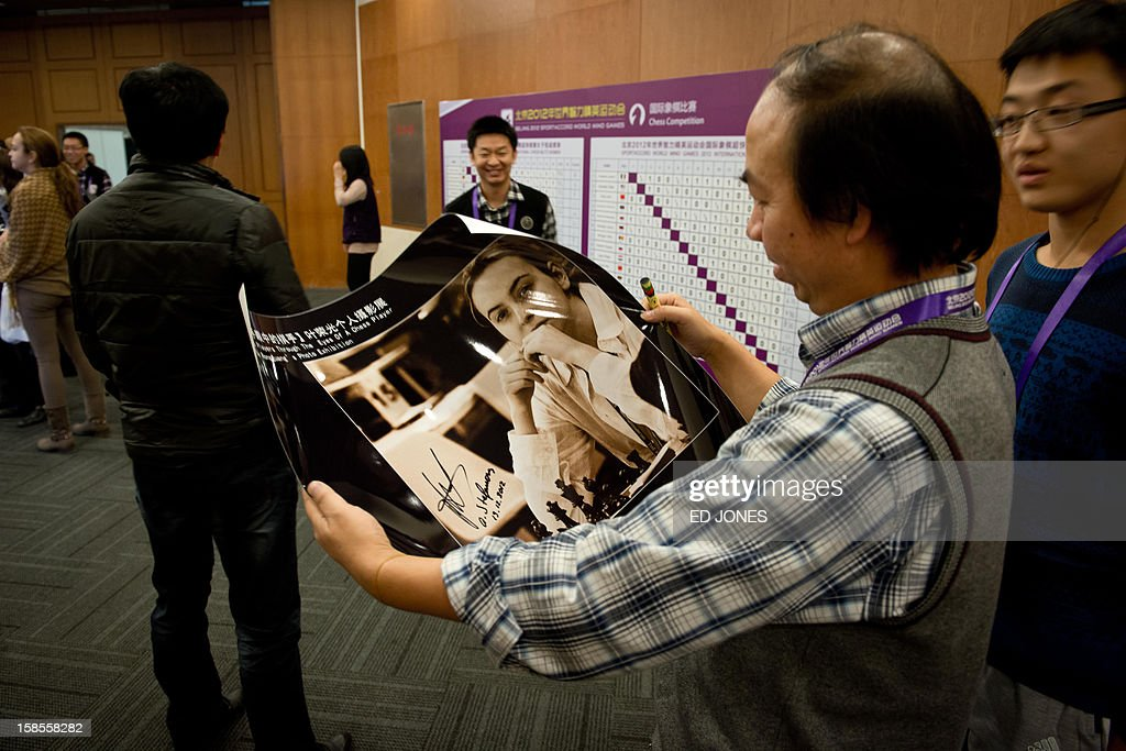 A chess fan holds a signed portrait of Antoaneta Stefanova of Bulgaria as she takes part in a 'blinfold' chess tournament at the Beijing 2012 World Mind Games Tournament in Beijing on December 19, 2012. Some of the world's top chess players went eye-to-eye in the year's highest-level 'blindfold' chess tournament -- seen by some as the toughest challenge in the game. Unable to physically see their own or their opponent's past moves, the players summoned headache-inducing levels of concentration to fight for gold in a silent conference room, lined up in front of laptop screens showing a blank board. AFP PHOTO / Ed Jones
