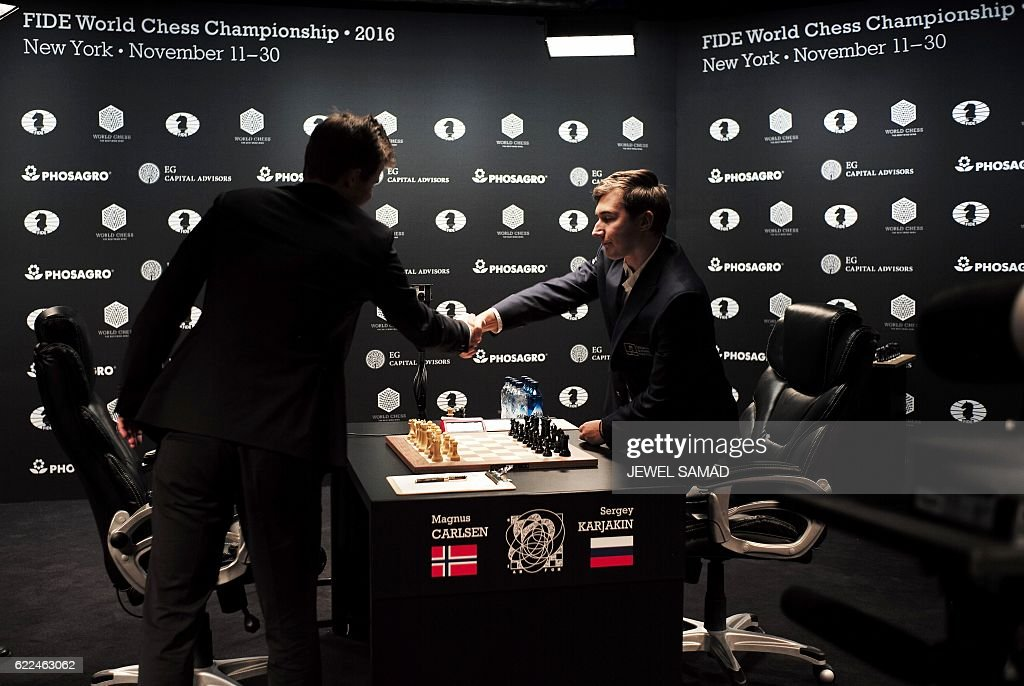 Chess grandmaster and current world chess champion Magnus Carlsen (L) of Norway shakes hands with challenger Sergey Karjakin of Russia before their World Chess Championship 2016 round 1 match in New York on November 11, 2016. / AFP / Jewel SAMAD