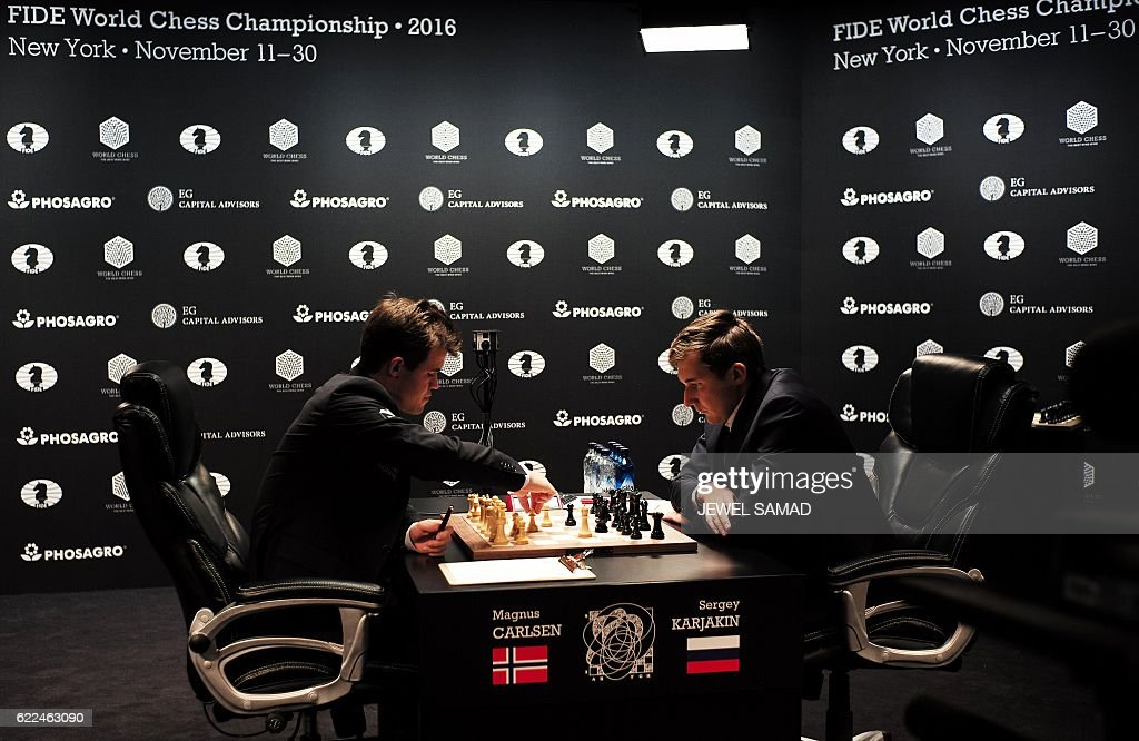 Chess grandmaster and current world chess champion Magnus Carlsen (L) of Norway moves a piece on the board against challenger Sergey Karjakin of Russia during their World Chess Championship 2016 round 1 match in New York on November 11, 2016. / AFP / Jewel SAMAD