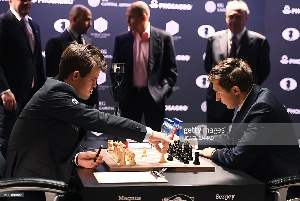 Chess grandmaster and current world chess champion Magnus Carlsen of Norway moves a piece on the board against challenger Sergey Karjakin of Russia during their World Chess Championship 2016 round 1 match in New York on November 11, 2016. / AFP / Jewel SAMAD