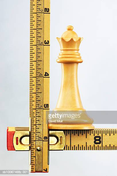 Chess king piece on folding ruler, studio shot, close up