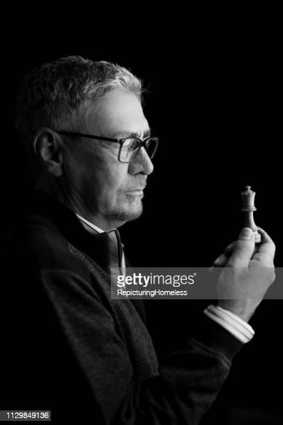 Ein Schachmeister wird in Gedanken begraben, während er ein Stück Schach in der Hand betrachtet.