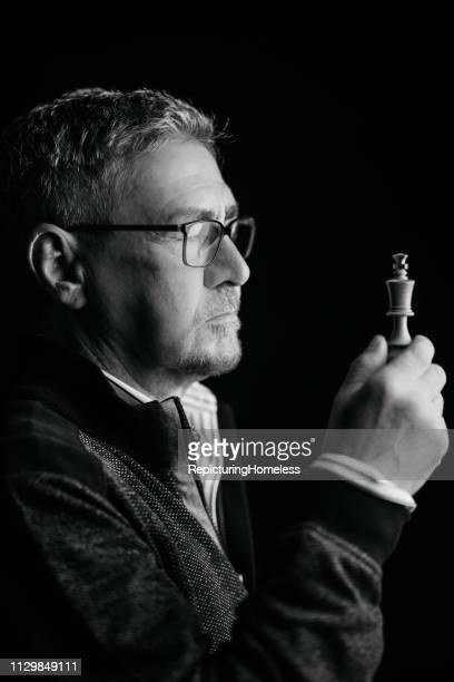 Ein Schachmeister schaut auf ein Stück Schach in der Hand