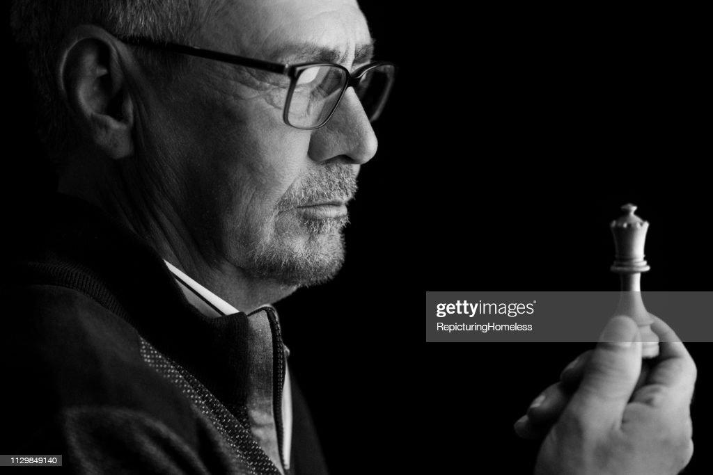 Ein Schachmeister schaut auf ein Stück Schach in der Hand, während er nachdenkt : Stock-Foto