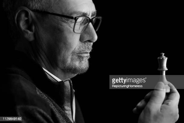 Ein Schachmeister schaut auf ein Stück Schach in der Hand, während er nachdenkt