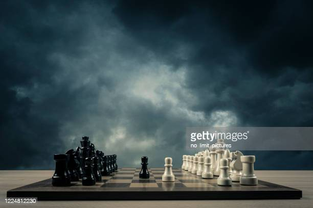 chess opening in front of storm clouds - chess board stock pictures, royalty-free photos & images