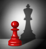 Chess pawn with the shadow of a king.