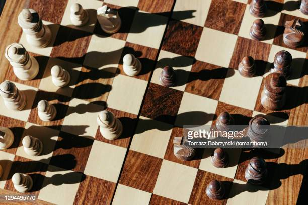 chess pieces casting shadows on a chessboard - chess board stock pictures, royalty-free photos & images