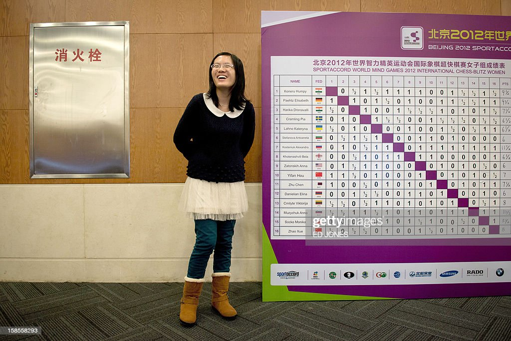 Chess player Hou Yifan of China stands beside a scoreboard following her win in a 'blinfold' chess tournament at the Beijing 2012 World Mind Games Tournament in Beijing on December 19, 2012. Some of the world's top chess players went eye-to-eye in the year's highest-level 'blindfold' chess tournament -- seen by some as the toughest challenge in the game. Unable to physically see their own or their opponent's past moves, the players summoned headache-inducing levels of concentration to fight for gold in a silent conference room, lined up in front of laptop screens showing a blank board. AFP PHOTO / Ed Jones