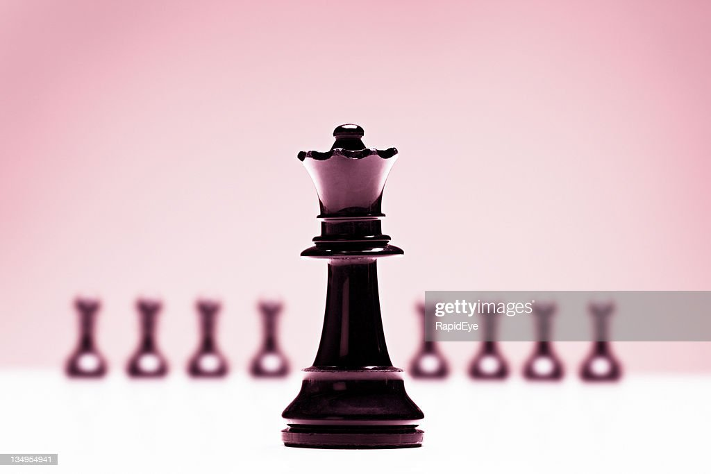 Chess queen in front of pawns on pink background : Stock Photo