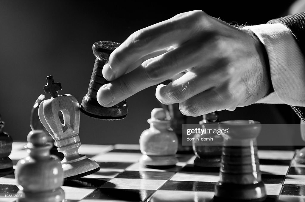Chess Strategy, Chess player, businessman making checkmate move, black white : Stock Photo