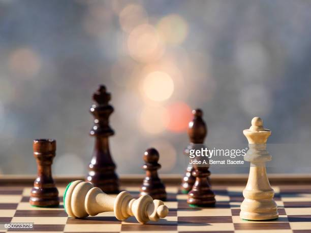 chessboard on a table (checkmate),  illuminated by the light of the sun outdoors - chess board stock pictures, royalty-free photos & images