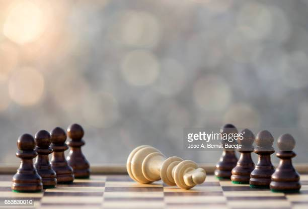 Chessboard on a table (checkmate),  illuminated by the light of the Sun outdoors
