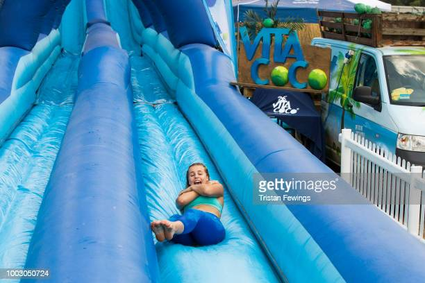 Festival goers relax at Vita Coco's Slip N' Slide during Lambeth Country Show at Brockwell Park on July 22 2018 in London England Vita Coco bought...