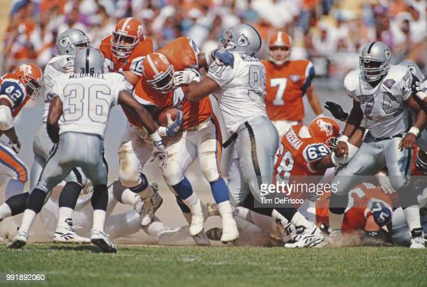 Chester McGlockton Defensive Tackle for the Los Angeles Raiders tackles Derrick Clark Running Back for the Denver Broncos during their American...