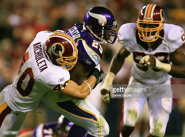 Chester Taylor of the Minnesota Vikings gets tackled by Adam Archuleta from the Washington Redskins on the first Monday Night Football game of the...