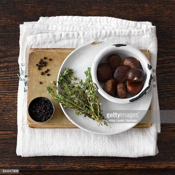 chestnuts, plate, thyme, book, black pepper, kitchen towel - chestnut food stock pictures, royalty-free photos & images