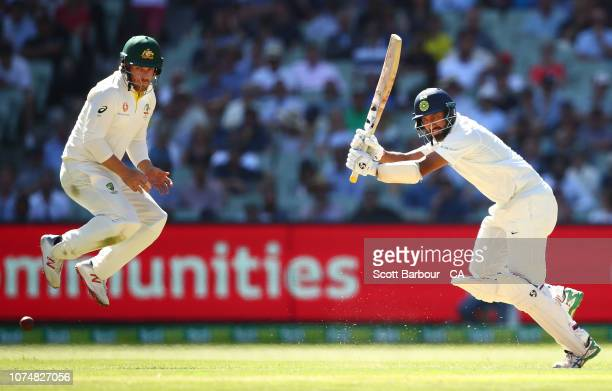 Cheteshwar Pujara of India bats as Aaron Finch of Australia jumps during day one of the Third Test match in the series between Australia and India at...