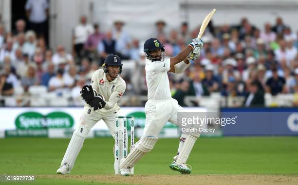 Cheteshwar Pujara of India bats watched by England wicketkeeper Jos Buttler during day three of the Specsavers 3rd Test match between England and...