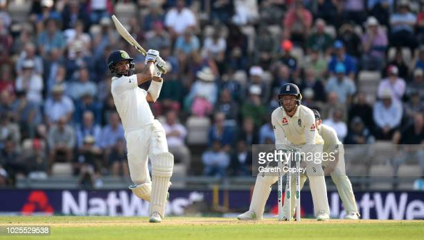 Cheteshwar Pujara of India bats watched by England wicketkeeper Jos Buttler during day two of the Specsavers 4th Test match between England and India...