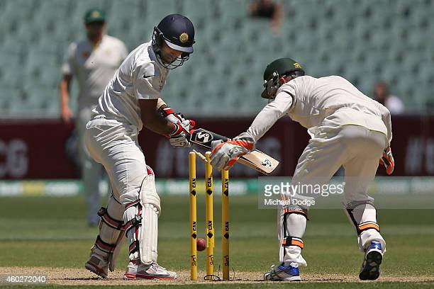 Cheteshwar Pujara of India is bowled by Nathan Lyon of Australia as wicket keeper Brad Haddin celebrates during day three of the First Test match...