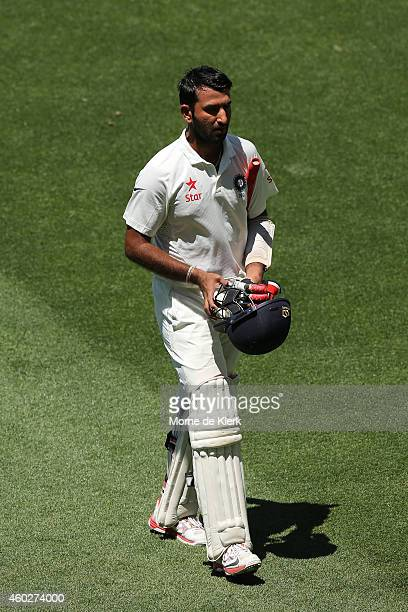 Cheteshwar Pujara of India leaves the field after getting out to Nathan Lyon of Australia during day three of the First Test match between Australia...