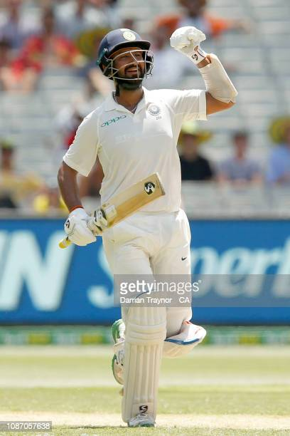 Cheteshwar Pujara of India raises his bat after scoring 100 runs during day two of the Third Test match in the series between Australia and India at...