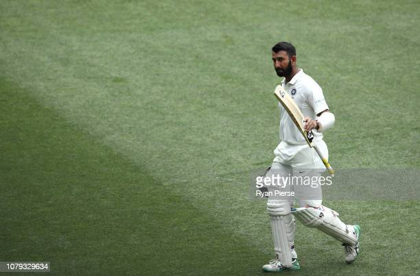 Cheteshwar Pujara of India raises his bat as he leaves the ground after being dismissed for 71 runs by Nathan Lyon of Australia during day four of...