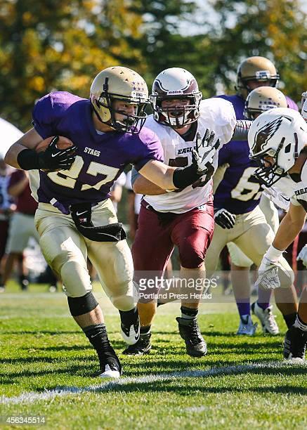 Cheverus player Joe Fitzpatrick runs past Windham defensive players Patrick Leavitt left and Tanner Laberge right at Cheverus High School on Saturday...