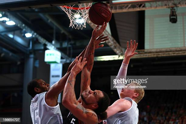 Chevon Troutman of Muenchen shoots against Sharrod Ford of Bamberg and his team mate Philipp Neumann during the Beko Basketball match between Brose...