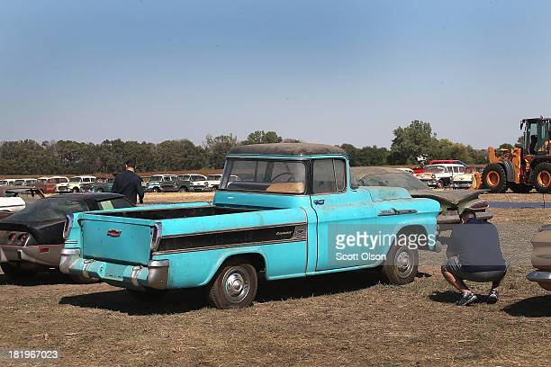 Chevrolet Cameo truck with one mile showing on the odometer is lined up for auction with other cars and trucks in a field on the Lambrecht family...
