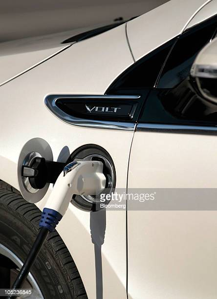 A Chevrolet Volt is charged at a public electric vehicle charging station outside the headquarters of General Motors Co at the Renaissance Center in...