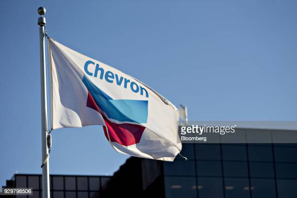 A Chevron Corp flag flies outside an office building in Midland Texas US on Thursday March 1 2018 Chevron the world's thirdlargest publicly traded...