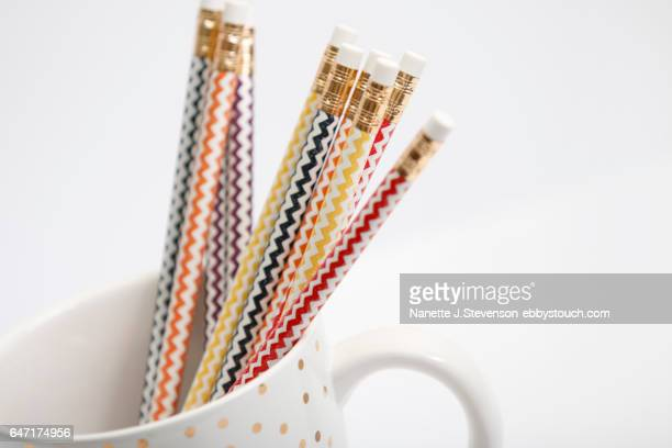 chevron patterned pencils in gold coffee cup - nanette j stevenson stock photos and pictures