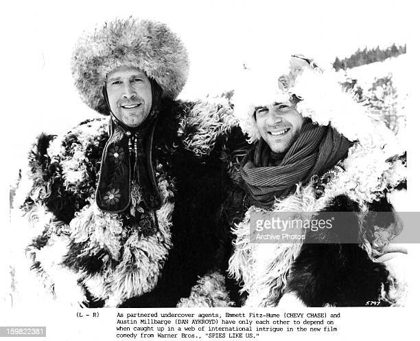 Chevy Chase and Dan Aykroyd wear heavy fur coats in a scene from the film 'Spies Like Us' 1986