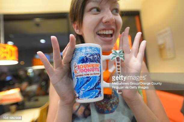 Cheyann Dillon shows off her new mug during opening day at the new Dunkin' Donuts in Santa Monica on Tuesday. This is the first full expression...