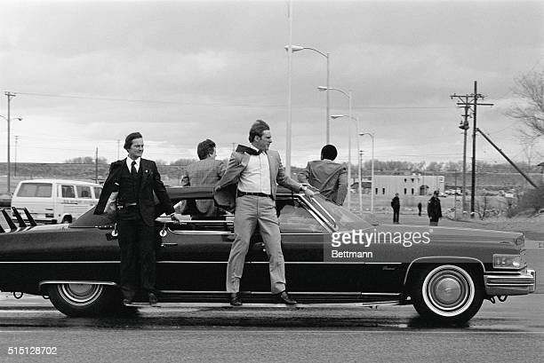 Secret Service agents cling to car which follows President Ronald Reagan's auto to airport here President Reagan addressed a crowd at Storey Gym and...