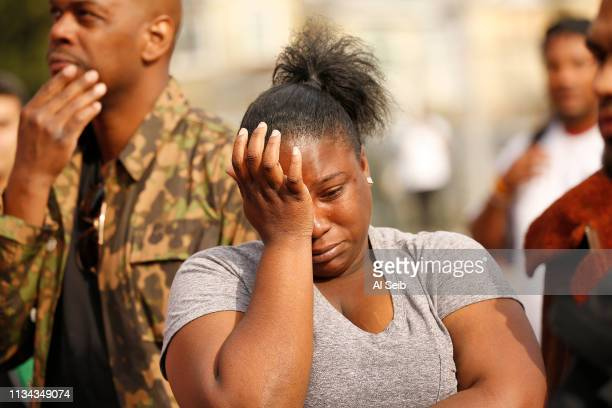 Cheyna Allen wipes tears as mourners gather on April 1 2019 in Los Angeles California Monday morning in the parking lot at 3420 W Slauson where...