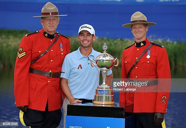 Chez Reavie poses with the winner's trophy and two Royal Canadian Mounted Police 'Mounties' after winning the RBC Canadian Open at the Glen Abbey...