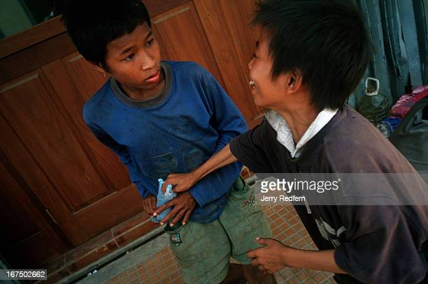Chhien right jokingly tries to grab a plastic bag of glue away from Along who is stoned and confused from taking a big hit of glue They both sniff...