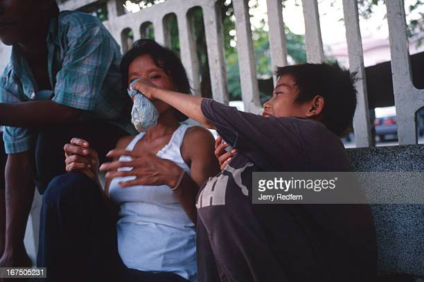 Chhien tries to get his 'Street Mom' Mao to sniff glue as they hang out on a streetside bench Mao says she does occasionally sniff glue too They are...