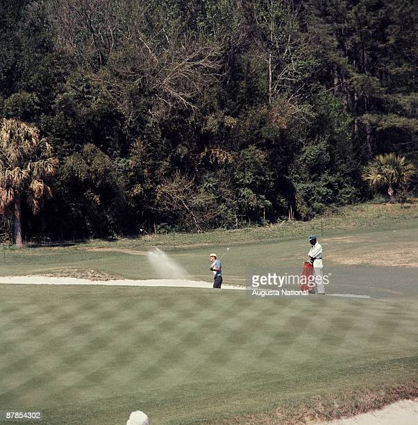 Chi Chi Rodriguez blasts out of the bunker next to his caddie during the 1963 Masters Tournament at Augusta National Golf Club 0n April 1963 in...