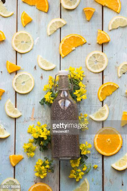 Chia drink in bottle and slice of orange and lemon on wood