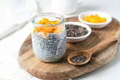 Chia pudding in glass jar with almond milk and mango on white background