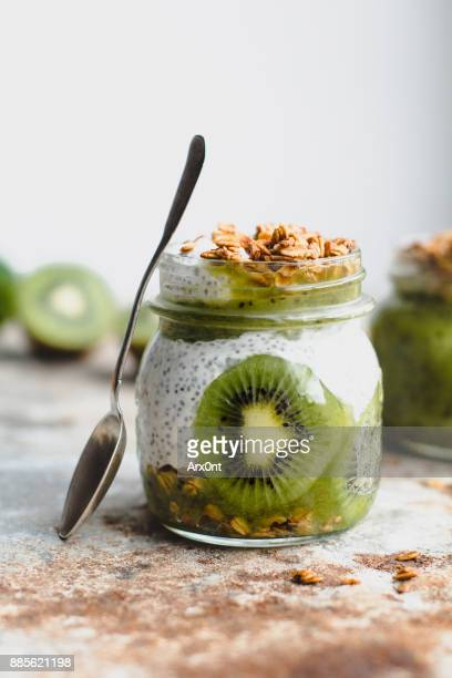 chia pudding with kiwi, granola and almonds in a jar - nut food stock photos and pictures